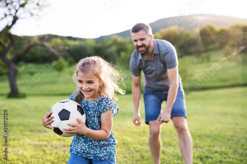 Father with a small daughter playing with a ball in spring nature Fototapeta
