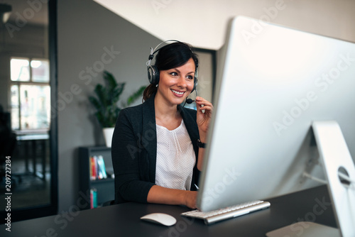 Fototapeta Female consulting manager with headset working in the office.
