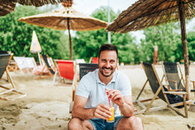 Young Smiling Man Sitting On A Beach Chair And Holding A Cocktail. Looking At Camera.