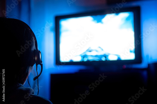 Young male gamer with glasses and headset playing video game at home in the dark room using game console controller watching at LED TV Poster