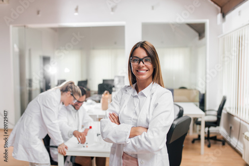 Portrait of female scientist or medical worker, colleagues in the background Fototapeta