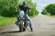 Moto biker and his motorcycle on asphalt road