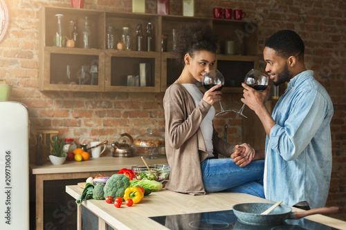 Loving african-american couple drinking wine in kitchen. Canvas-taulu