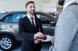 Waist up portrait of smiling handsome car salesman giving car keys to client standing in showroom of luxury dealership