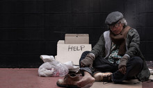 The Beggar Sleeping Against The Wall With Fatigue, Cardboard And Text Are Nearby