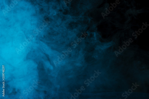 Poster Fumee mysterious and bright cloud of blue steam on a dark background
