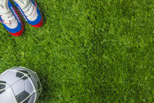 Footballer Boots And Ball On Green Grass Top View