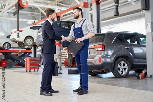 Full length portrait of handsome businessman shaking hands with worksman while standing in production workshop of modern car factory, copy space