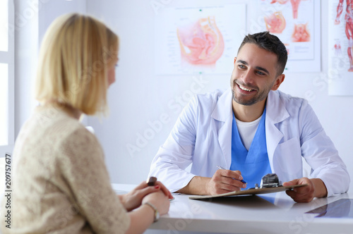 Handsome doctor is talking with young female patient and making notes while sitt Tableau sur Toile