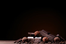 Chocolate Pieces With Coffee Beans And Candy Balls On Wooden Table
