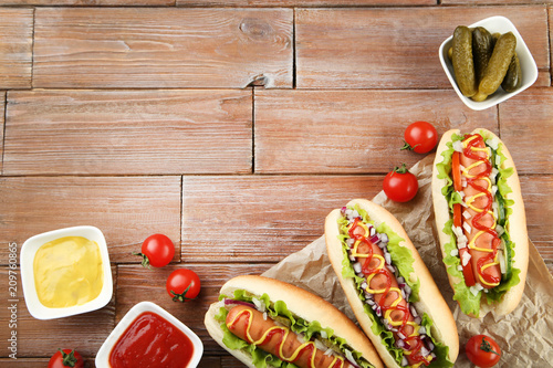 Photo  Hot dogs with ketchup, mustard and vegetables on wooden table