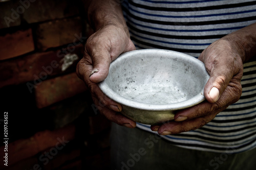 The poor old man's hands hold an empty bowl Fotobehang