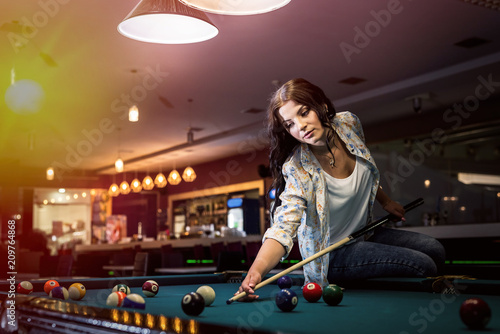 Foto Woman sitting on billiard table going make a hit