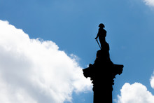Statue Of Lord Horatio Nelson In Silhouette On A Column In Trafalgar Square London, Against A Blue Sky With Clouds