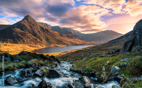 In de dag Diepbruine A rushing river flowing through the mountains of wales