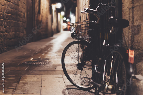 Poster Fiets retro bicycle in the night old city on background bokeh light flare in night architecture, vintage bike in evening street in barcelona town, cycle transportation in defocus backdrop, travel concept