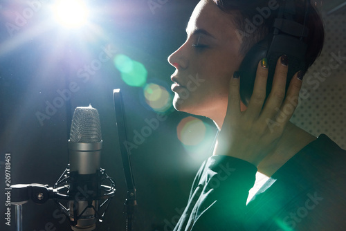 Fotomural Side view of beautiful girl with eyes closed wearing earphones while singing song with microphone in studio