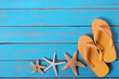 Flip flops starfish old distressed bright blue beach wood background