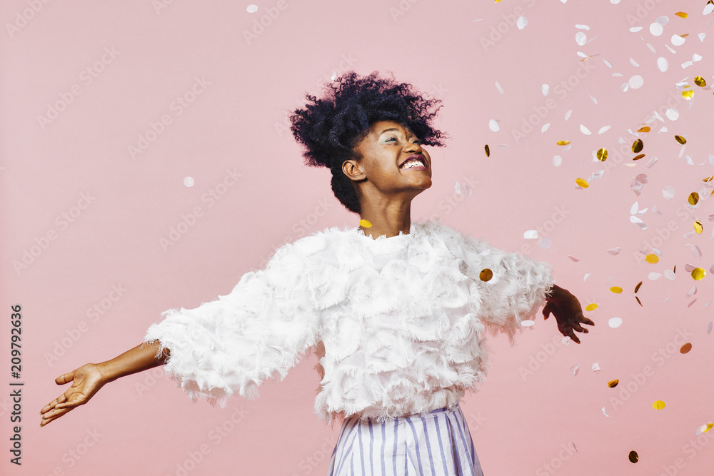 Fototapeta A magical time - Portrait of a very happy girl with arms out, smiling at confetti falling