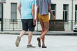 retail of couple mix , african and caucasian walking on the street holding hands on back view