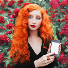 Young Beautiful Unusual Redhead Girl With Very Long Curly Hair On A Background Of A Bush Of Red Roses. A Slender Woman With Pale Skin With And Mobile Phone In Hands. Summer Background