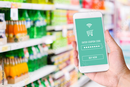 Hand holding smartphone with E-coupon, discount coupon on screen device over blur grocery background, shopping on line promotion, on line shopping, digital marketing, business and technology concept