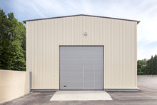 Facade Of Industrial Storehouse With Closed Gray Metal Gate And Door