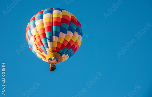 In de dag Ballon Colorful Hot Air Balloon Flying High in a Clear, Blue Sky, Firing Off the Burners to Gain Elevation