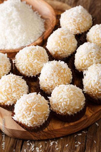 Keuken foto achterwand Snoepjes Brazilian Coconut Kisses (Beijinhos de Coco) condensed milk and coconut flakes close-up. Vertical