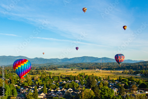 Fotografie, Obraz  Six Hot Air Balloons Flying Over Town to the Grants Pass Balloon & Kite Festival