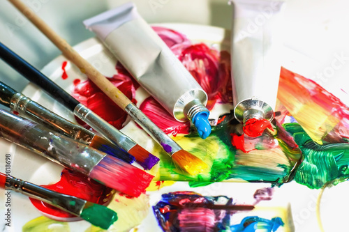 Used palette of the artist with mixed colors of acrylic paints close-up as an artistic background.