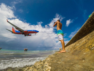 Muscular man on the coast watching landing of airplane flying over the sea of caribbean sea. Montego Bay. Jamaica. 2017