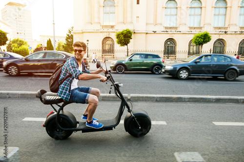 Fototapeta premium młody mężczyzna jedzie pojazdem elektrycznym