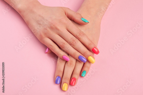 Poster Manicure Female hands with colorful polish nails. Woman well-groomed hands with multicolor nails on salon table. Manicure nail painting.