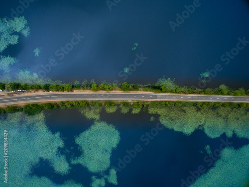 Foto auf AluDibond Blaue Nacht Landscape of an asphalt road. View from above on the road going along the blue river. Summer photography with bird's eye view