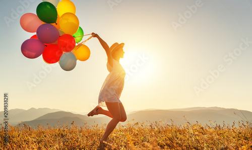Photo  happy woman with balloons at sunset in summer