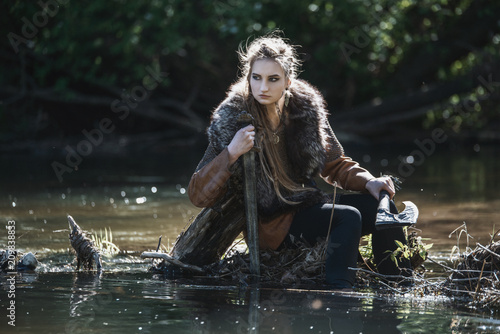 Photo  Viking woman with sword and hammer wearing traditional warrior clothes in a deep mysterious forest
