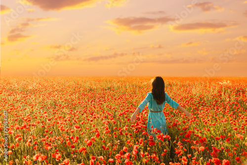 Papiers peints Lieu connus d Asie Woman walking in red poppies meadow at sunset.
