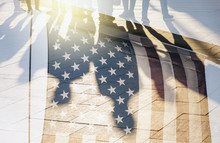 Shadows Of People In A Street And Flag Of The USA As Background Concept Toned Picture