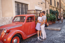 Young Beautiful Couple Stands Near A Red Car On Trastevere Street In Rome Italy