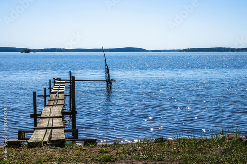 A small jetty / pier in a lake. Warm sunny day with the sun standing high.