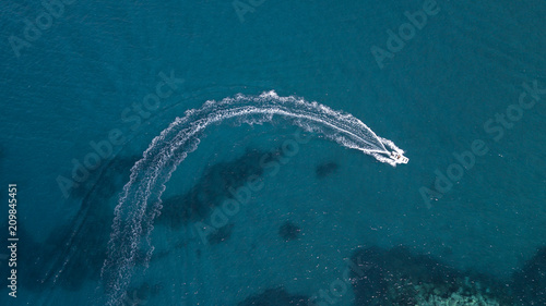 Fotografia Aerial view of a white motorboat running on the azure waters of the Tyrrhenian Sea