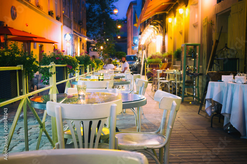 Fotomural Outdor restaurant terrace at night old European city street.