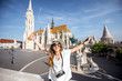 Portrait of a young woman tourist with photo camera in front of the famous Mattias church traveling in Budapest
