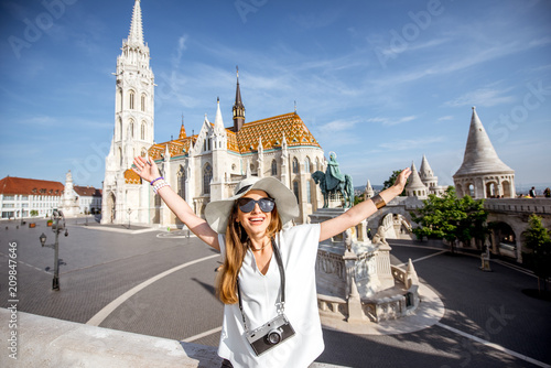 Fototapety, obrazy: Portrait of a young woman tourist with photo camera in front of the famous Mattias church traveling in Budapest