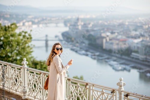 Montage in der Fensternische Budapest Young woman photographing beautiful morning view on Budapest city from the Gellert hill in Hungary