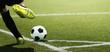 Leinwandbild Motiv Foot of a child football player and ball on the football field, kicking a corner kick