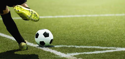 Stopa dziecka piłkarz i piłka na boisku piłkarskim, kopiąc rzut rożny