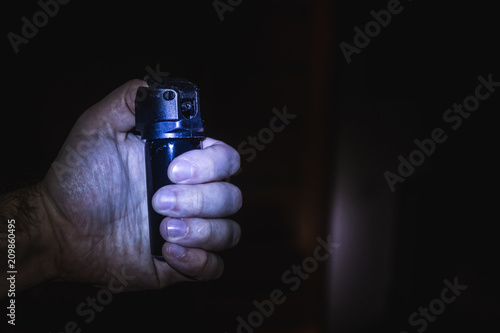 a man's hand holds a gas pepper spray in the dark, a black background. concept of safety and self-defense