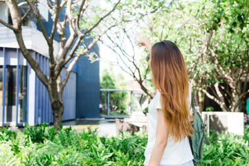 Fototapeta A young Asian woman enjoying in the garden for her city lifestyle on weekend morning. Young woman with her weekend city lifestyle in garden. Outdoor activity and city lifestyle concept.